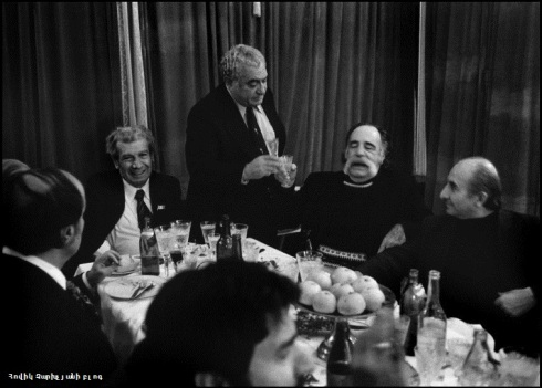 Saroyan being toasted by his friends, standing is the film Director Sergei PARADJANOV.