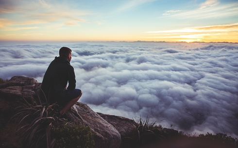 guy-looking-out-on-clouds-from-top-of-mountain